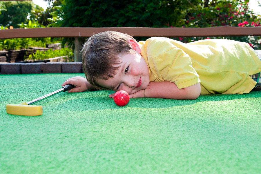 Young boy plays mini golf on putt putt course.